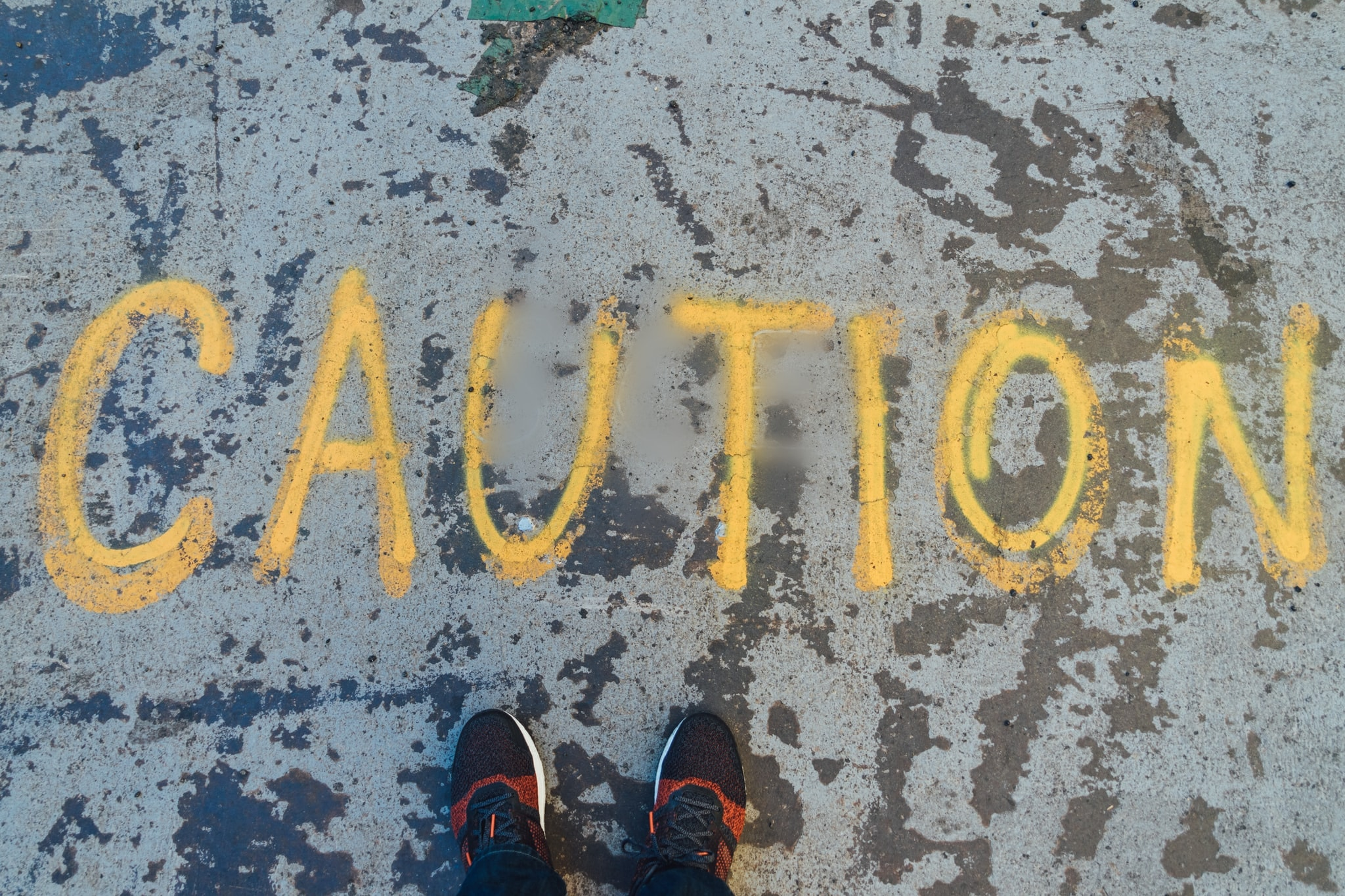 the word Caution spray painted on a concrete floor