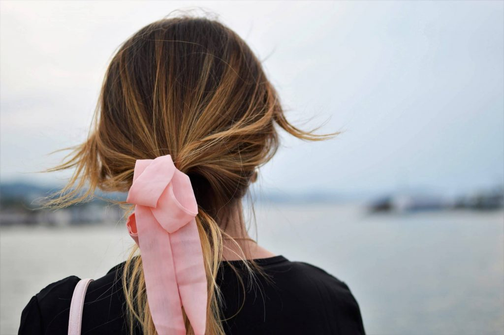 back of woman with pink bow in hair